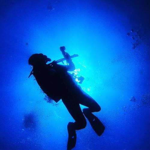 Commercial diver swimming in a darkened recess of the ocean.